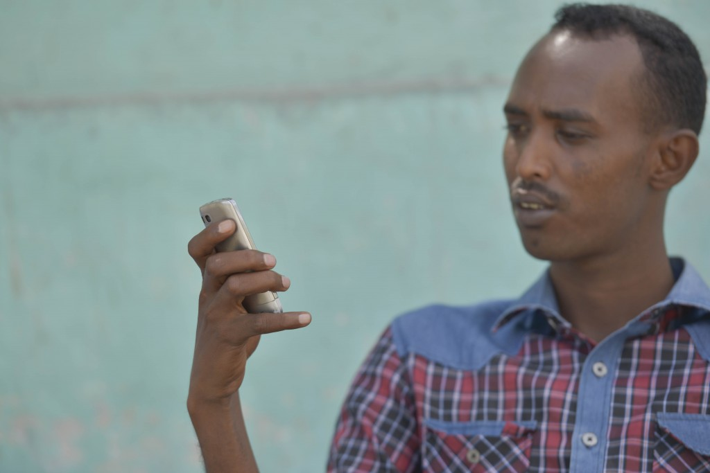 Africa, Somalia - Deeq Ahmed Shire on his phone at a street tea shop at the Jardiinka bar quatro square in downtown Mogadishu during his tea break.  The Alshabaab have banned the use of internet mobile usage on all mobile devices thereby affecting the use of 3G services which have just been rolled out by mobile service providers. He says that he can't live without internet as it connects him with his family and friends outside Somalia. AU UN IST PHOTO/ David Mutua